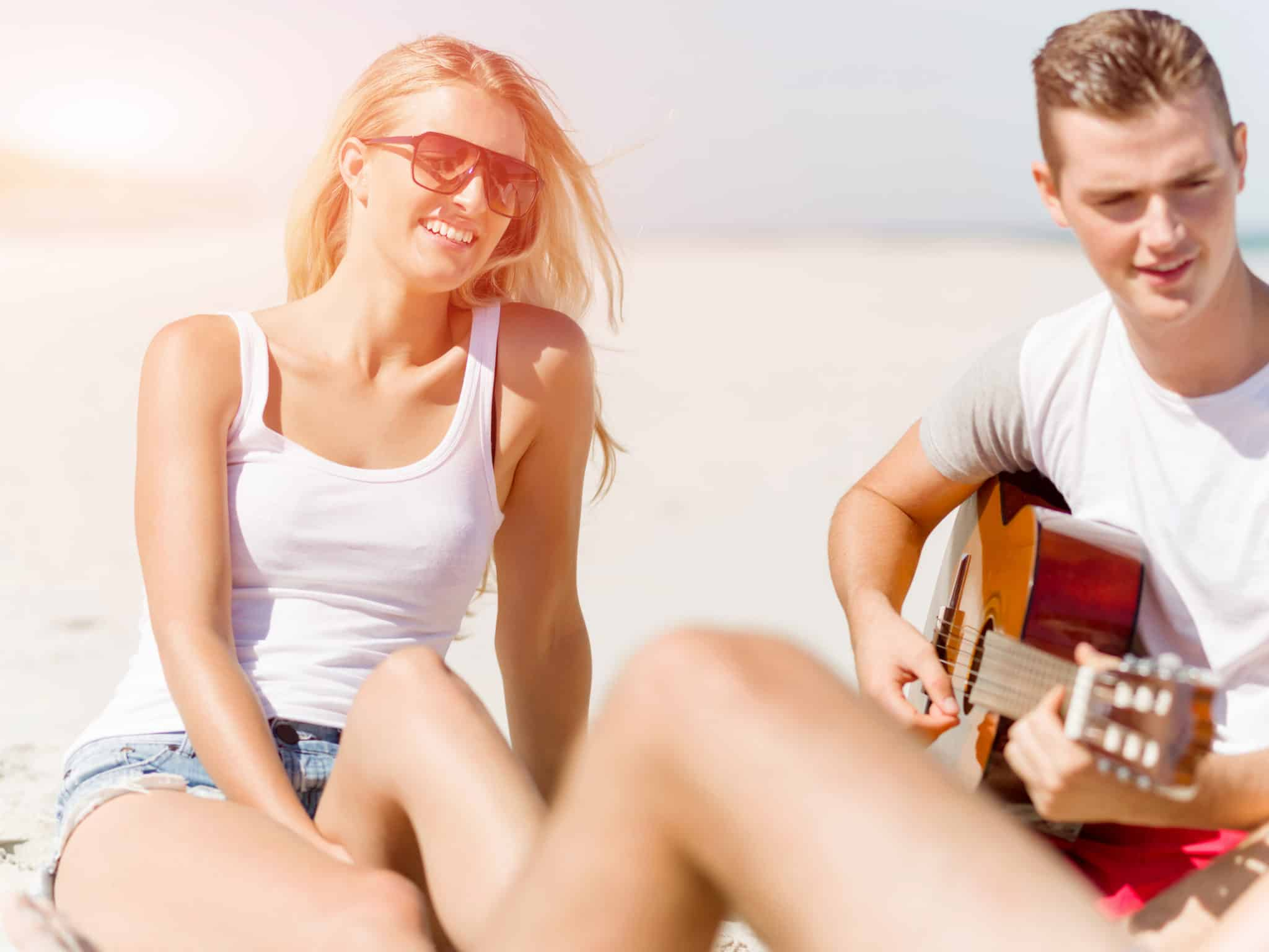how to do long distance relationships couple playing guitar on the beach